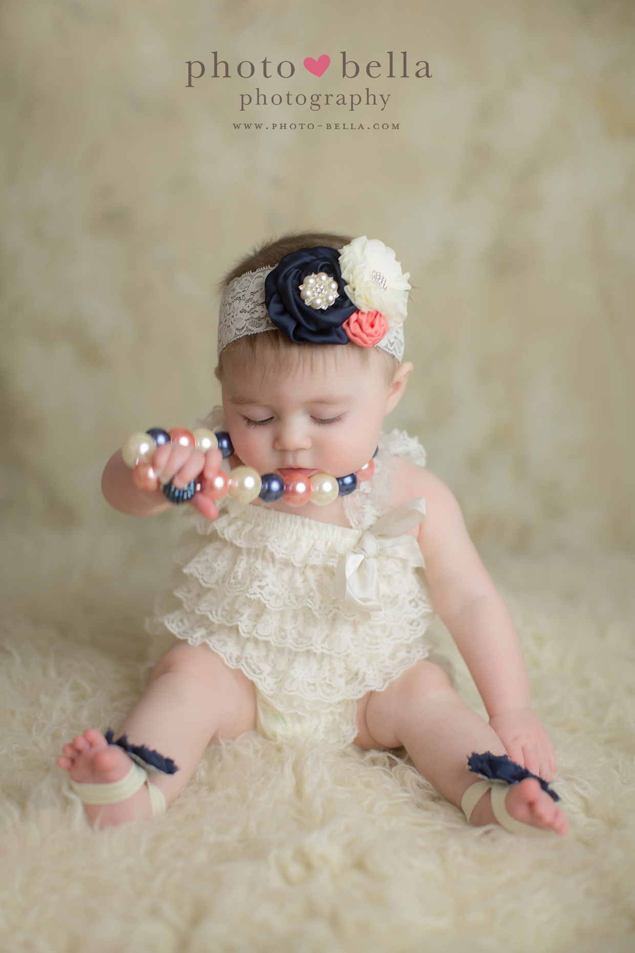 photo of six month old baby playing with necklace